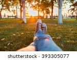 Stock photo male feet in gumshoes on green grass in the park at sunset 393305077
