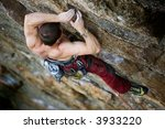 A male climber, viewed from above, climbs a very high and steep crag. - stock photo