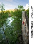 An eager female climber on a steep rock face looks for the next hold. Breathtaking scenery including a lake and forest are in the background. - stock photo