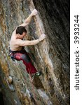 Male climber at the top of a very tall rock wall (crag) - stock photo