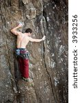 A male climber against a large rock face climbing lead. - stock photo