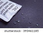 Small photo of Close up silica gel or desiccant in paper bag on black background