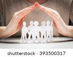 paper people under hands in... | Shutterstock . vector #393500317