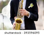 hands of groom play on saxophone | Shutterstock . vector #393596095