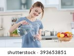 Young Woman Pouring Water From...