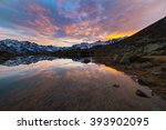 Small photo of High altitude alpine lake in idyllic land once covered by glaciers. Reflection of snowcapped mountain range and scenic colorful sky at sunset. Wide angle shot taken on the Italian Alps at 2200 m asl.