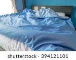 unmade bed with white pillow... | Shutterstock . vector #394121101