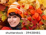 Girl in autumn orange hat on leaf group with flower.  Outdoor. - stock photo