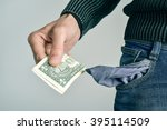 Small photo of a young caucasian man in jeans taking one US dollar out of his pocket