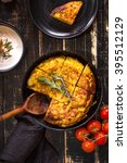 Small photo of Tortilla de patatas in a pan with garlic sauce aioli and fresh tomatoes cherry. Traditional spanish dish. Omelette with eggs, potatoes and onion. Rustic black background. Top view