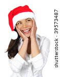 Surprised Christmas Woman. Very beautiful surprised woman with santa hat holding her head in amazement and Looking to the side. Isolated on seamless white background. - stock photo