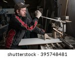 Small photo of Saint-Petersburg, Russia - March 17, 2016: In a furniture factory carpenter making additive. process drilling holes in the cylindrically shaped furniture fronts for the installation of accessories.