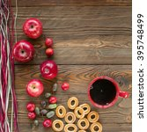 Small photo of red cup of black tea and ripe red apples, actinidia berries, bagels on wooden table with decorative colorful dry straw. top view. free space for text