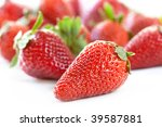Strawberries over white background, with shallow depth of field.  Focus on front strawberry. - stock photo