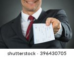 Small photo of Close-up Of Businessman Hands Giving Cheque In Office