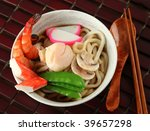 Seafood Udon Noodle Soup, Popular Japanese Dish, with shrimp, crab meat, scallop, fish cake, snow peas, mushrooms in broth - stock photo