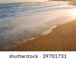 Wave foam and golden sand on the shore. Punta del Este beach - stock photo