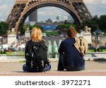 Young tourist couple sitting in front of Eiffel tower in Paris France - stock photo