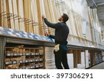 Carpenter selecting lengths of cut wood of a rack in a hardware store , low angle rear view from the side