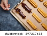 Small photo of Eclairs or profiterole with chocolate and whipped cream preparing on baking sheet. Spreading chocolate on top of eclair with spoon. Traditional French dessert. Empty space for design text template.