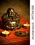 statue of happy Buddha, two candles and ying yang symbol over red bamboo background - stock photo