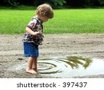 Curly haired little girl playing in a mud puddle - stock photo