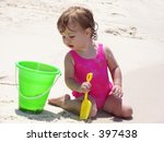 Little girl on the beach peering curiously into a bucket - stock photo