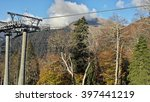 Cable way in the Caucasian mountains, autumn nature, peaks in the haze of clouds - stock photo