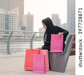 Small photo of Middle Eastern woman in abaya checking her shopping bags