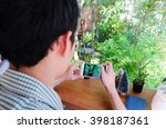 A Man Taking Photo Of Plant...