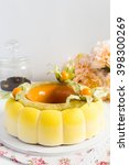 Small photo of Yellow french mousse cake covered with chocolate velour and caramel glaze decorated with physalis. Modern european cake. Shallow focus