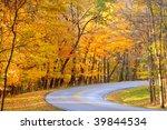 Brilliant autumn colors along the curve of a park road - stock photo