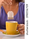 Small photo of Woman soaking tea bag on yellow cup, preparing hot tea.Dipping teabag on cup.