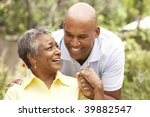 senior woman being hugged by... | Shutterstock . vector #39882547