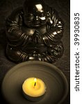 statue of Buddha with candle in old color tonality - stock photo