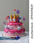 Small photo of A fancy birthday cake with a candyland theme. The three layer cake is covered with fondant and candy decorations