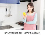 young attractive asian woman who cooks while watching a smart phone in a kitchen