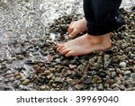 Two Small Feet On Pebbles On...
