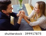 Small photo of Young couple in love sharing a tender moment clasping hands across the table and smiling into each others eyes