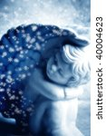 little angel with snow flakes in blue tonality - stock photo