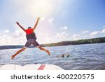 kids jumping off a boat into... | Shutterstock . vector #400220575