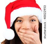 Christmas girl very excited and surprised holding her mouth. Beautiful mixed asian / caucasian model. - stock photo