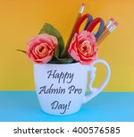 Small photo of A white coffee mug filled with office supplies like pencils and a pair of scissors with a couple of silk roses on a blue and yellow background. Happy administrative professional'??s day message