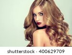 Small photo of Beautiful girl with long wavy hair . fair-haired model with curly hairstyle and fashionable makeup . Bright purple lips