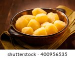 Small photo of Bowl of whole boiled baby potatoes on a rustic wooden table for serving as an accompaniment to a meal