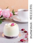 Small photo of Mini mousse cakes covered with chocolate velour and decorated with rose bud. Modern european cake with coffee. Shallow focus