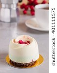 Small photo of Mini mousse pastry cake covered with white chocolate velour and decorated with freeze-dried raspberries. Modern european cake. Shallow focus