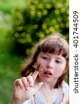 Small photo of Little girl looks at a butterfly. Aglais urticae L.