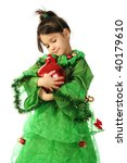 Little smiling girl in green Christmas tree costume with red Christmas decoration - stock photo