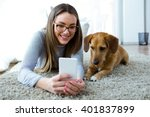 Stock photo portrait of beautiful young woman with her dog using mobile phone at home 401837899
